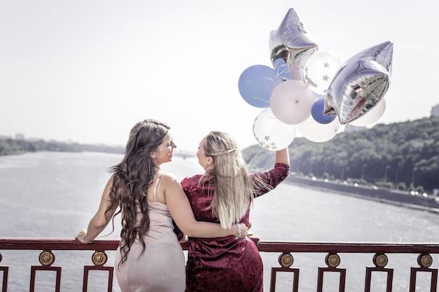 Лучшие друзья. позитивные радостные женщины обнимают друг друга, стоя вместе на мосту