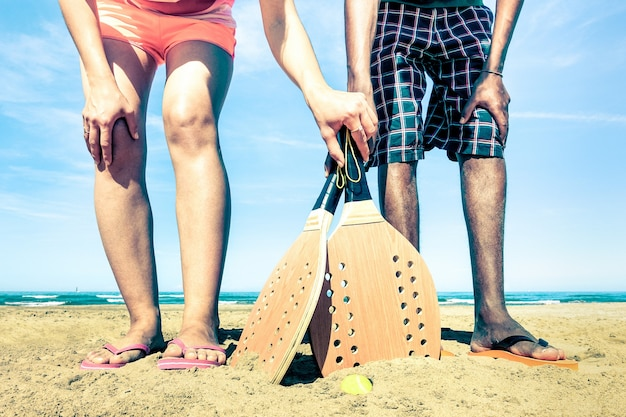 Best friends ready to play beach tennis game at beginning of summer