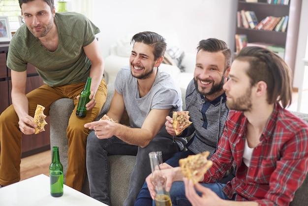 Migliori amici che riposano con birra e pizza
