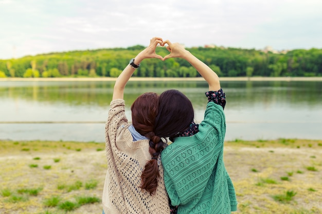 Best friends showing heart sign over beautiful landscape on the
