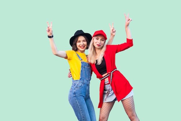 좋은 시간을 함께 보내는 가장 친한 친구. 카메라를 바라보며 서서 v 노래를 보여주는 두 명의 아름다운 행복한 유행 힙스터 소녀의 초상화. 실내 스튜디오 촬영, 녹색 배경에 고립.