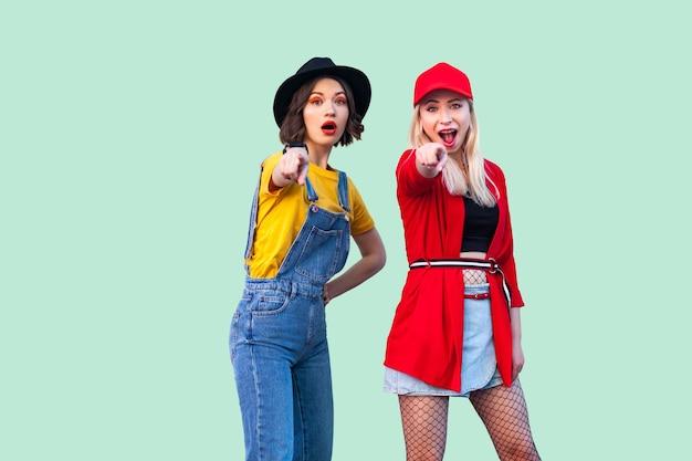 좋은 시간을 함께 보내는 가장 친한 친구. 두 명의 아름다운 세련된 힙스터 소녀들이 서서 당신에게 손가락을 가리키며 카메라를 바라보고 있습니다. 실내 스튜디오 촬영, 녹색 배경에 고립.