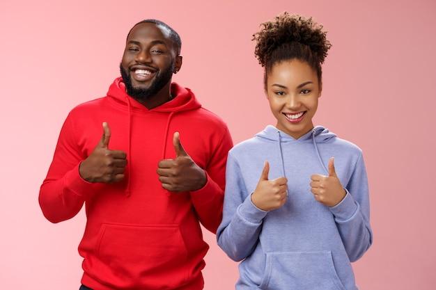親友はあなたの選択をサポートします。誇らしげに満足している肖像画は、見栄えの良いアフリカ系アメリカ人の男性女性がカメラの親指を立てて笑って、素晴らしい購入を好み、ピンクの背景に立って広く応援しています