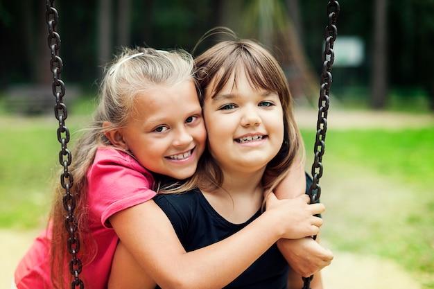 Best friends swinging in a park