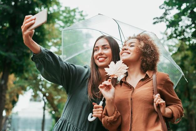 Migliori amici che si fanno un selfie sotto l'ombrellone