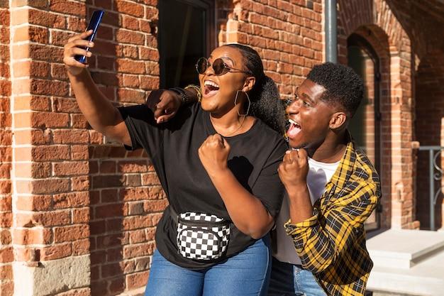 Best friends taking a selfie together outside