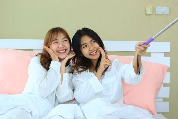 Best friends teenage joyful with selfie on bed