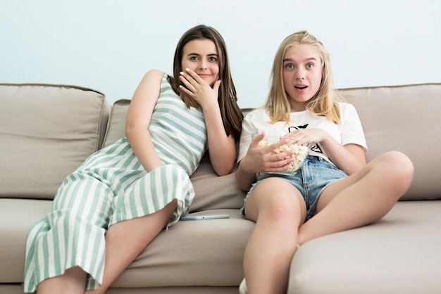 Best friends watching a movie on the sofa