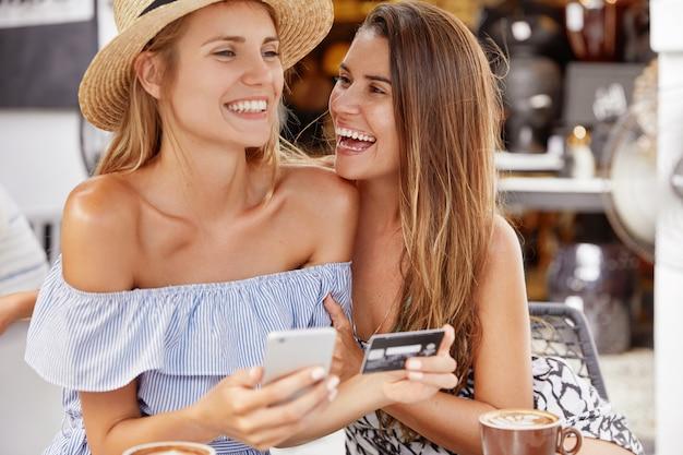 Лучшие подруги-женщины встречаются в кафетерии, счастливы делать покупки в интернете с помощью смартфона и пластиковой карты