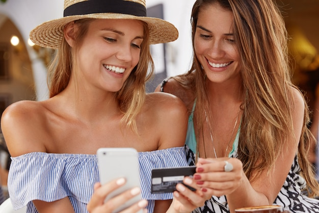 最高の友達の女性がカフェテリアで集まり、スマートフォンとプラスチックカードでオンラインショッピングを楽しんでいます