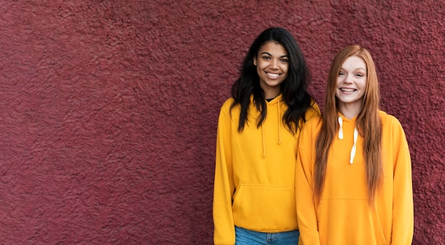 Best friends in yellow hoodies with copy space