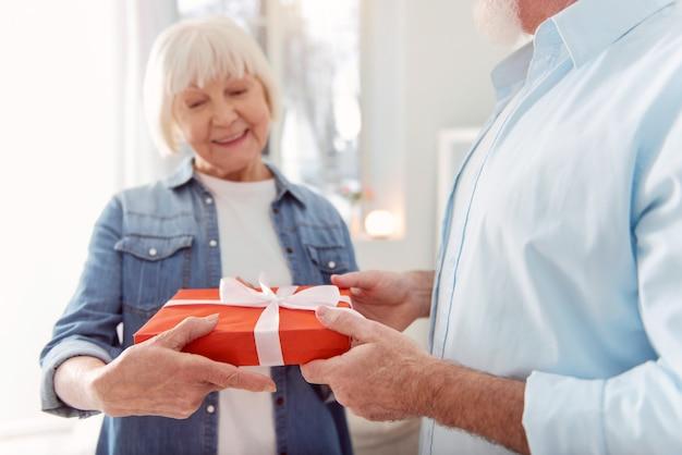 最高の贈り物。彼の誕生日に彼を祝福する彼の最愛の妻から贈り物を受け取っているしっかりした造りのハンサムな男の手に焦点を当てています