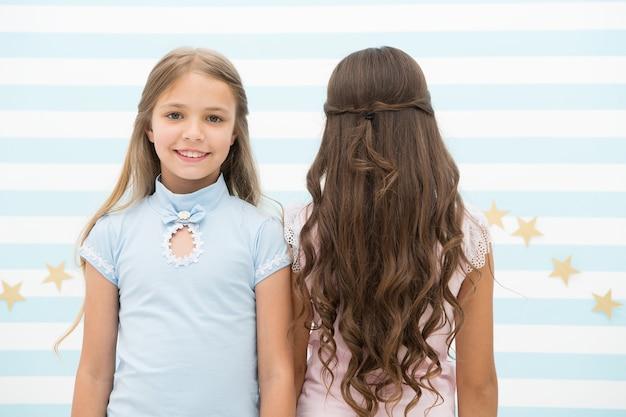 긴 머리를위한 최고의 헤어 스타일. 놀이방에서 긴 갈색 머리와 금발 곱슬 머리를 가진 귀여운 작은 소녀. 사랑스러운 작은 아이들은 긴 느슨한 머리. 긴 곱슬 머리를 즐기고 있습니다. 프리미엄 사진