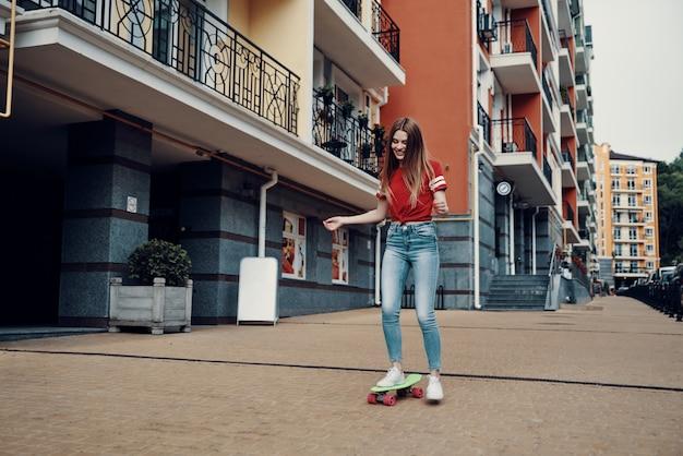 Лучшее хобби на свете. полная длина привлекательной молодой женщины, улыбаясь во время катания на скейтборде на открытом воздухе