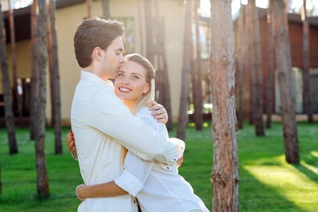 最高の夫。彼女にキスしながら彼の最愛の妻を抱き締める素敵な思いやりのある夫