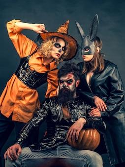 Лучшие идеи для хэллоуина. группа позирует с тыквой. модный гламур на хэллоуин. портрет счастливой молодой группы в хеллоуине с тыквой.