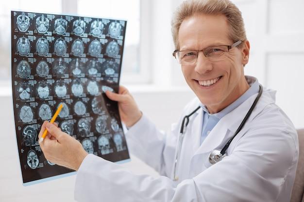 私のドメインで最高。患者の診断を理解しながら彼が手に持っている脳スキャンを研究しているハンサムで陽気な著名な専門家