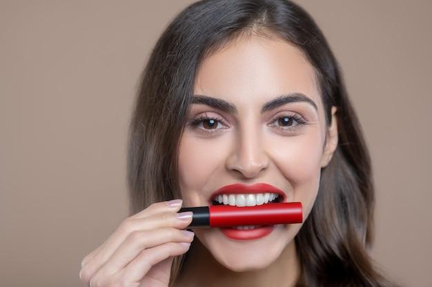 最高のリップグロス。歯に赤いリップグロスを保持している陽気な若いきれいな女性の顔をクローズアップ