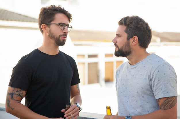 Best male friends discussing issues over bottle of beer