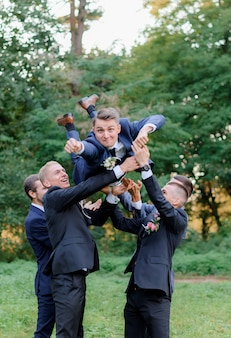 Best men are throwing up groom outdoors in the park, funny wedding day
