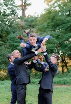 I migliori uomini stanno vomitando lo sposo all'aperto nel parco, divertente giorno delle nozze