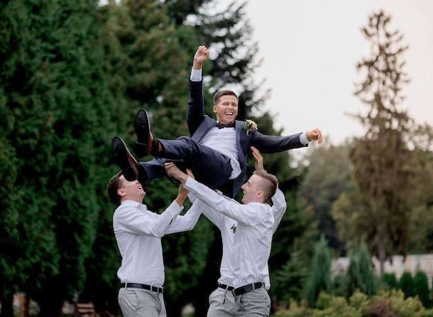 Лучшие мужчины подбрасывают улыбки жениха в парке на свежем воздухе