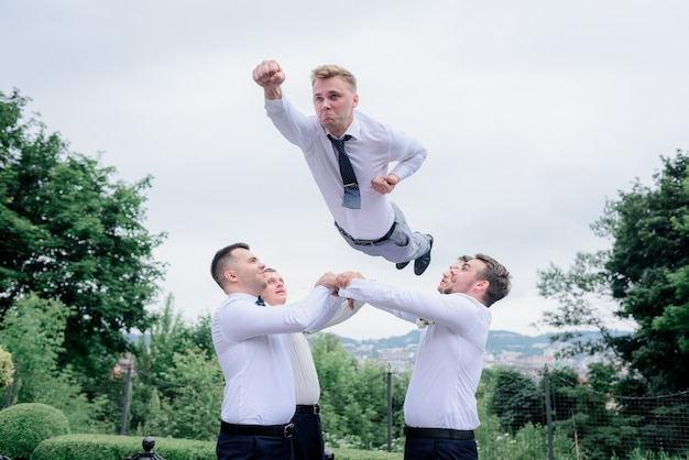 Best men dressed in formal attires are throwing the groom like a superman, outdoors, teamwork