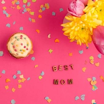 カップケーキと花の近くの最高のお母さんの言葉