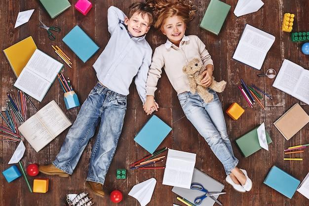 최고의 순간 아이들은 책과 장난감 근처에 누워 손을 잡고 카메라를 보고 웃고 있습니다.