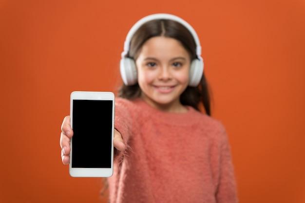 무료 최고의 음악 앱. 무료로 들어보세요. 음악 계정 구독을 받으세요. 수백만 곡에 대한 액세스. 음악 개념을 즐기십시오. 완벽한 사운드를 즐기십시오. 여자 아이는 음악 현대 헤드폰과 스마트폰을 듣습니다.