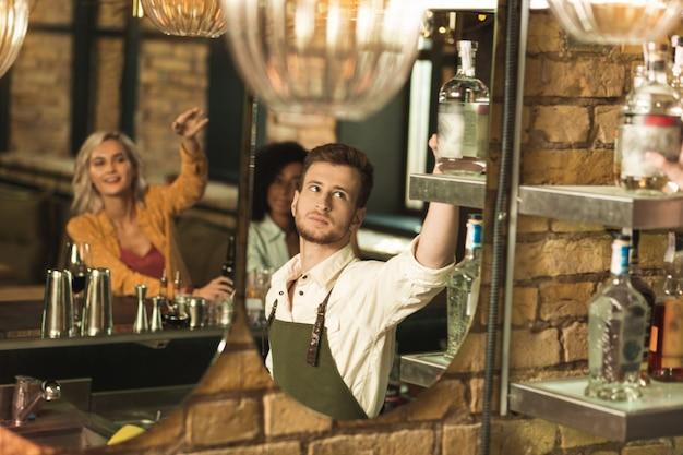最良のオプション。顧客が飲み物を選択している間、棚からアルコールのボトルを取り出してカクテルに追加する楽しい若いバーテンダー