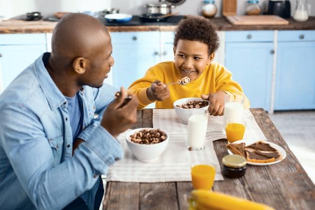 一日の最高の部分。陽気なプレティーンの少年が父親の隣のテーブルに座って、笑顔を交換しながら彼と一緒に穀物を食べる