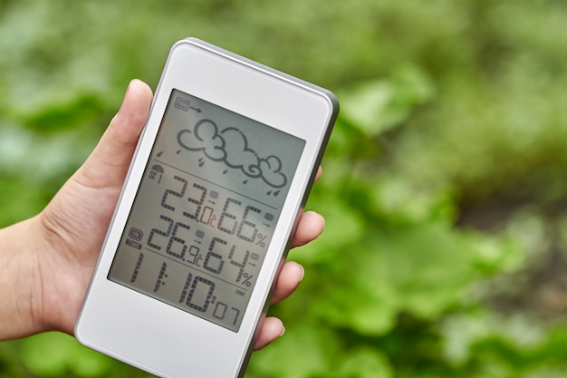 Best personal weather station device with weather conditions inside and outside. a girl holds a gadget in her hand on a background of green foliage.