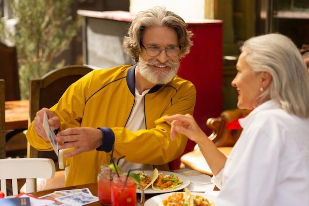 최고의 사진. 수염 난 남자가 거리 카페에서 아내와 함께 앉아 좋아하는 사진을 보여주고 있습니다.