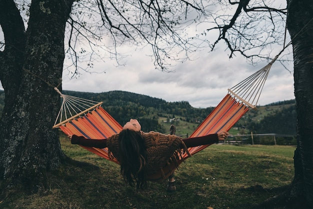 Best place to rest.  beautiful young woman lying in hammock while relaxing on the valley under the tree