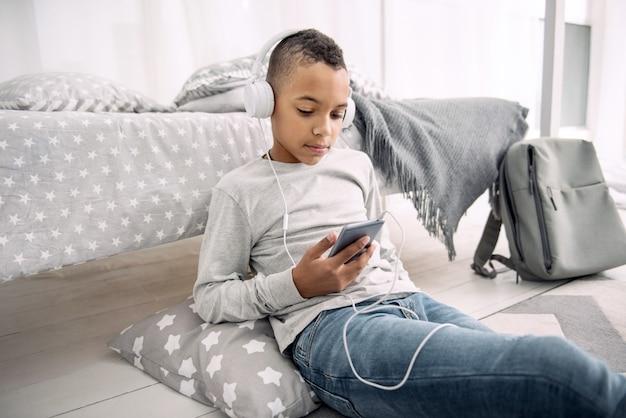 Лучший плейлист. амбициозный афро-американский мальчик в наушниках, глядя на экран телефона