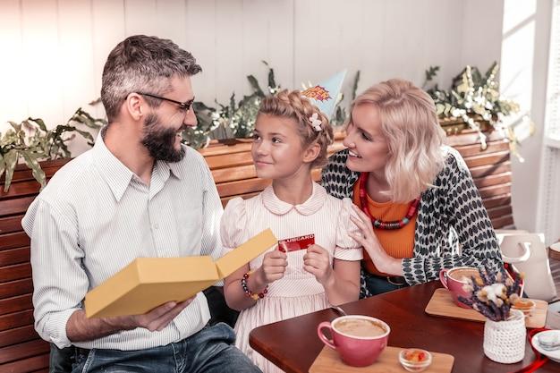 最高のプレゼント。彼女の両親と一緒に座っている間彼女の誕生日プレゼントを保持している素敵なポジティブな女の子