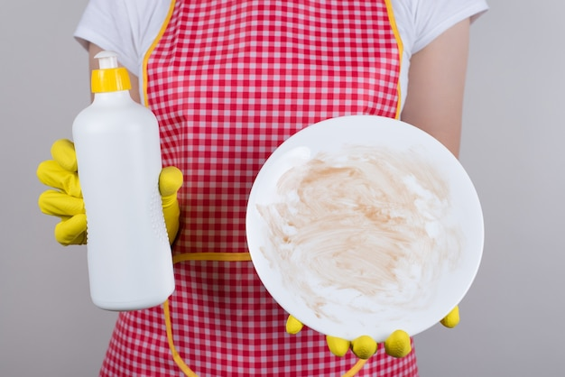 Best product for removing grease from crockery is using good detergent concept. cropped close up  of upset restaurant worker showing blank from chocolate sauce plate isolated grey wall