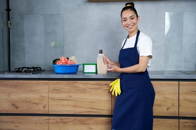 Лучшие продукты веселая молодая женщина, уборщица, улыбаясь в камеру, стоя с жидким бельем