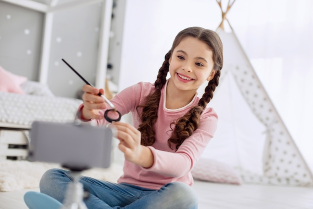 Best quality. pleasant lively pre-teen girl sitting cross-legged on the floor and showing her new eye shadows to her beauty blog audience