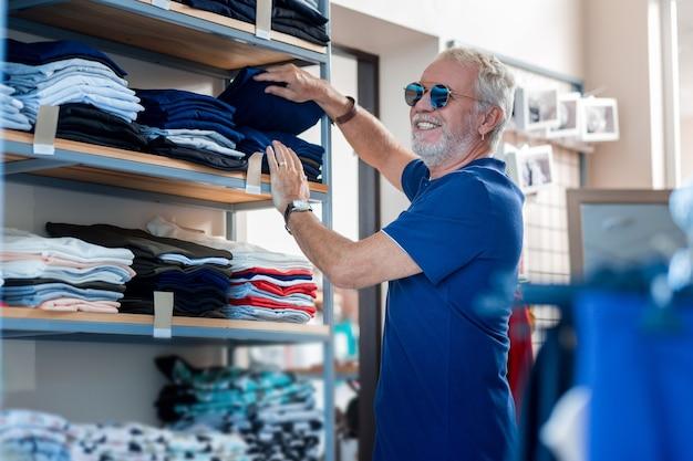 最高品質。好奇心を持ってサングラスを通して見ながら、ショッピングの棚でジーンズを選ぶ感情的な白髪の顧客の腰