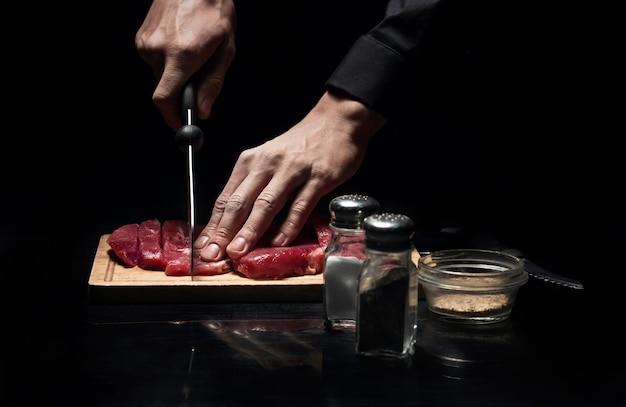 最高の領収書。レストランでの作業や調理中に肉を切り刻むシェフの手のクローズアップ。