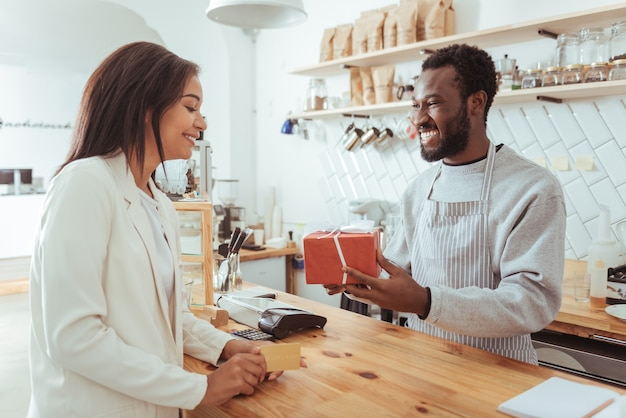 Best service. joyful pleasant barista giving his pretty female customer a box with her order while the woman holding a credit card, being ready to pay