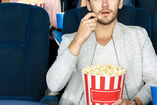 Best snack for cinema. cropped shot of a man eating popcorn in a movie theater