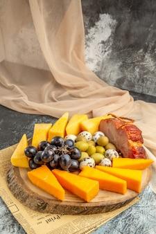 오래된 신문의 나무 갈색 쟁반에 다양한 과일과 음식을 넣은 최고의 간식