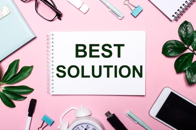 Лучшее решение записано в белом блокноте на розовом фоне в окружении деловых аксессуаров и зеленых листьев.