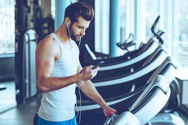 彼のトレーニングに最適な曲。ジムでトレッドミルに立っている間彼のスマートフォンを使用してスポーツウェアの若いハンサムな男の側面図 Premium写真