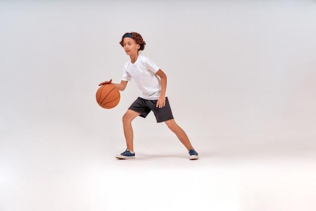 孤立して立っている間にバスケットボールをしている10代の少年のフルレングスショットの子供のための最高のスポーツ