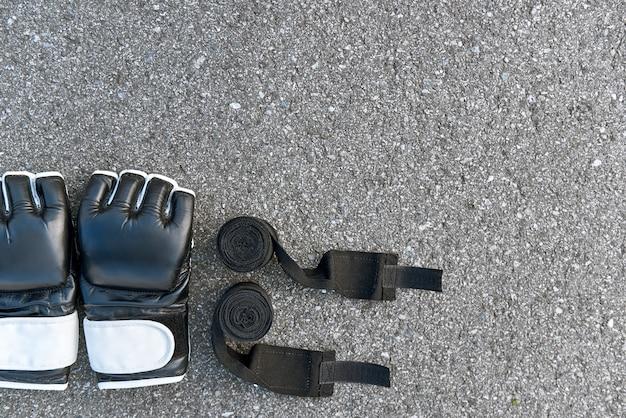 최고의 스포츠 아이템. 아스팔트 배경에서 권투 붕대가 있는 스포츠 권투 장갑의 클로즈업