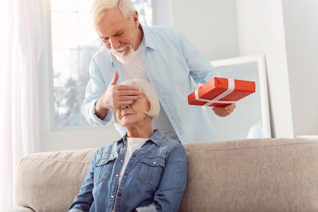 最高の驚き。妻の目を手で覆い、誕生日プレゼントを贈ろうとしている魅力的な思いやりのある年配の男性